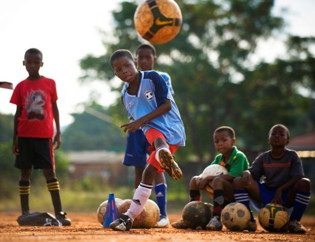 SA - A boy kicking a football, other boys sitting and standing around - CV Mamelodi.jpg